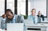 Fotografia tre genti di affari multietnica in cuffie con i computer portatili in ufficio moderno