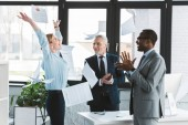 Fotografie excited multiethnic business people applauding and throwing papers in office