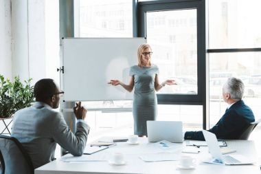 beautiful smiling businesswoman standing near whiteboard and looking at colleagues during business meeting