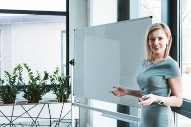 attractive businesswoman standing near blank whiteboard and smiling at camera