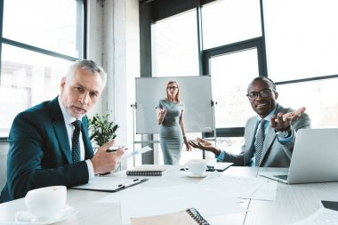 multiethnic business colleagues looking at camera while having conversation at business meeting