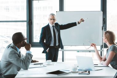 professional senior businessman pointing at whiteboard and looking at colleagues during business meeting