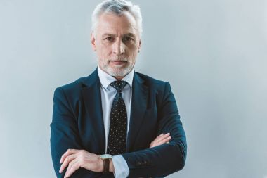 portrait of handsome senior businessman standing with crossed arms and looking at camera isolated on grey