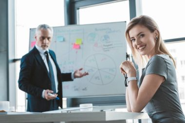beautiful businesswoman smiling at camera while senior businessman standing at whiteboard behind