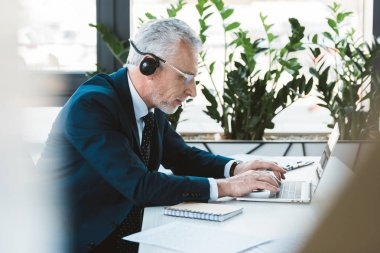 side view of senior businessman in eyeglasses and headset using laptop in office