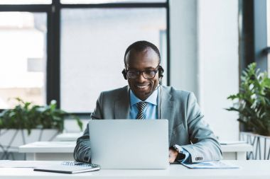 smiling african american businessman in eyeglasses and headset using laptop in office