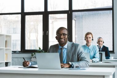 professional multiethnic business people in headsets using laptops and smiling at camera in office