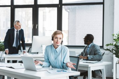 businesswoman in headset using laptop and looking at camera while male colleagues working behind in office