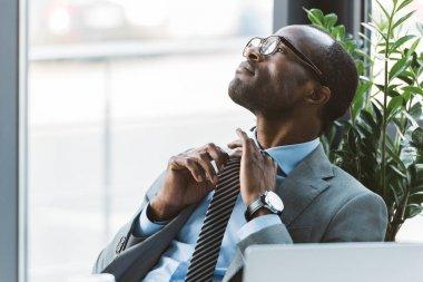 young african american businessman in eyeglasses adjusting necktie and looking away in office