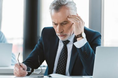 tired senior businessman with headache holding eyeglasses and looking down at workplace