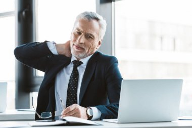 senior businessman suffering from pain in neck while working with laptop