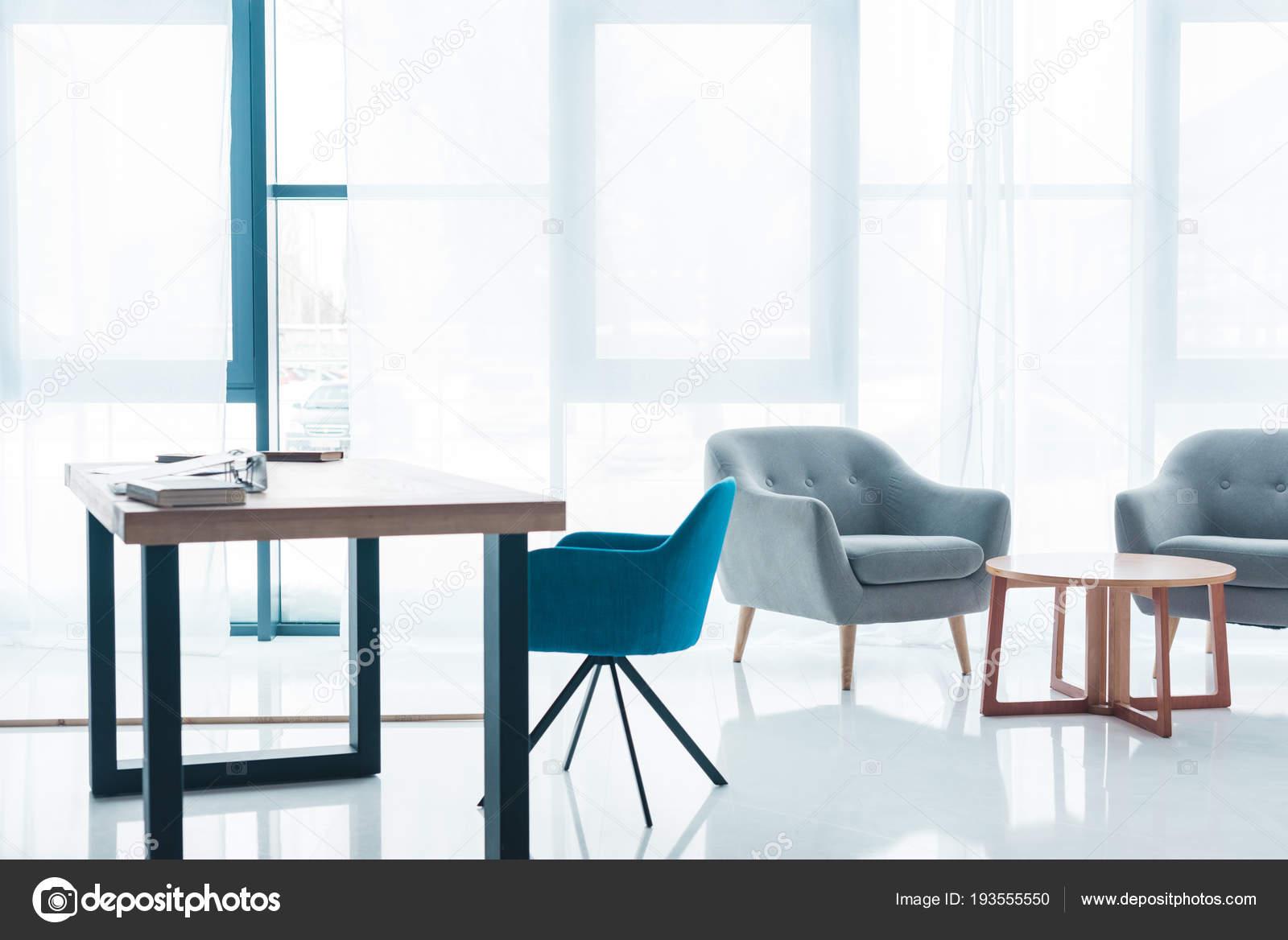 Table bois des fauteuils cosy vides intérieur bureau moderne