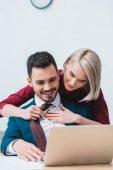 Fotografie krásný úsměv mladé spolupracovníky flirtování když spoli pracovali v kanceláři