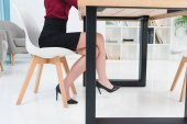 Fotografie cropped shot of young businesswoman in high heeled shoes sitting at workplace