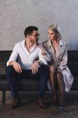sexy junge Frau in Mantel und Strümpfen flirtet mit schönen jungen Geschäftsmann sitzt auf dem Sofa
