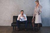 sexy Mädchen in Mantel und Strümpfen flirtet mit hübschen jungen Geschäftsmann sitzt auf der Couch