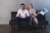 sexy Mädchen in Mantel und Strümpfen hält Zeitung in der Hand und flirtet mit hübschen Geschäftsmann