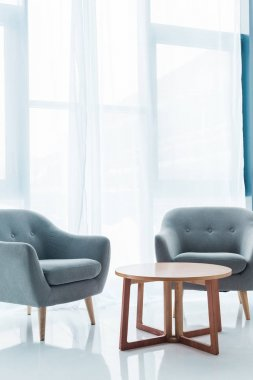 round wooden table and cozy empty armchairs in clean room