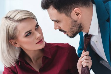 young business people looking at each other while businesswoman holding necktie of handsome businessman