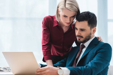 young coworkers using laptop and flirting in office