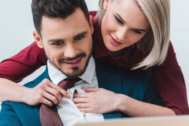 smiling young businessman and businesswoman flirting while working together