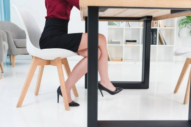 cropped shot of young businesswoman in high heeled shoes sitting at workplace