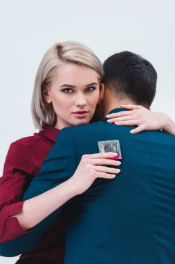 buisnesswoman holding condom and looking at camera while hugging with male colleague