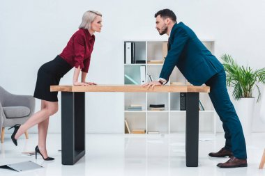 side view of young business people leaning at table and looking at each other in office