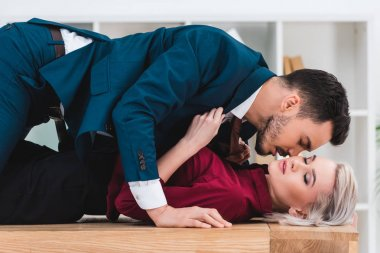 side view of sexy young couple kissing on table in office