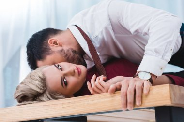 businessman kissing beautiful young businesswoman on table in office