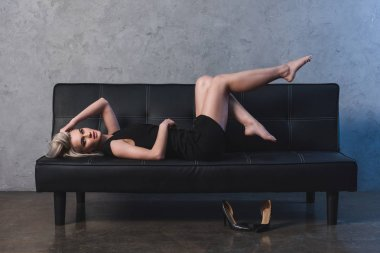 sexy blonde girl in black dress lying on sofa and looking at camera