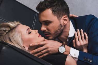 close-up view of sexy young couple able to kiss on couch in office