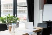 Fotografie notebook, dokumenty a láhve vody na stole v moderní kanceláři