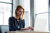 mosolyogva laptop hivatalban dolgozó szakmai üzletasszony