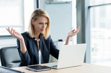 surprised businesswoman gesturing with hands and lookng at laptop in office