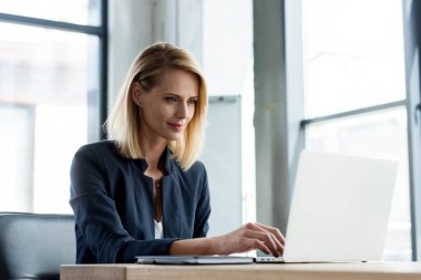 smiling professional businesswoman working with laptop in office