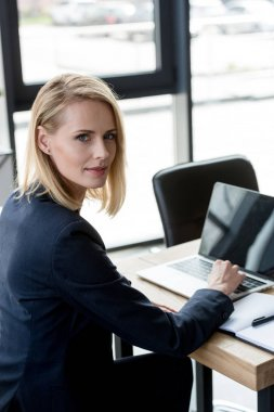 beautiful businesswoman using laptop and looking at camera in office