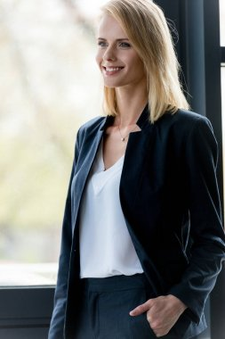beautiful smiling blonde businesswoman standing with hand in pocket and looking away