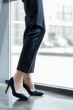 low section of businesswoman in high heeled shoes standing near window
