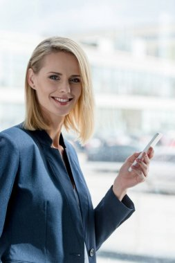 beautiful blonde businesswoman using smartphone and smiling at camera