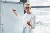 Fotografie Ernst senior geschäftsfrau in Brillen auf Whiteboard schreiben und Präsentation im Büro