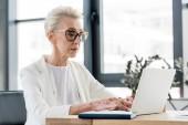 senior businesswoman in eyeglasses using laptop in office