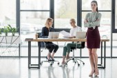 Photo beautiful young businesswoman standing with crossed arms at meeting in office