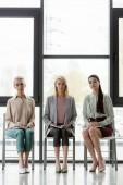 beautiful businesswomen sitting on chairs during meeting in office