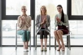 Fotografie beautiful three businesswomen applauding in office