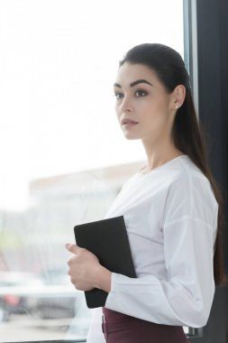 beautiful pensive young businesswoman holding notebook and looking away