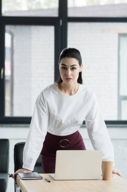 beautiful young businesswoman looking at camera while leaning at table in office