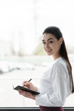 beautiful young businesswoman writing in notebook and smiling at camera