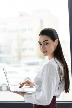 beautiful young businesswoman using laptop and smiling at camera