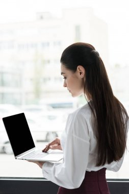 side view of young businesswoman using laptop with blank screen